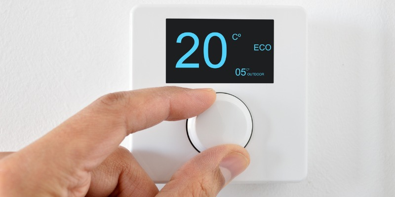 Hand turning down thermostat